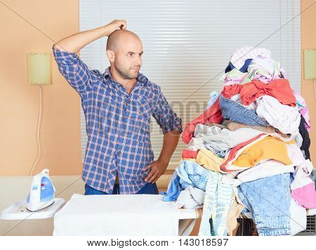 Caucasian Man Ironed Clothes In The Room Near The Window.