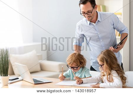 Nice picture. Contented mature man standing and watching how lovely girl and little boy drawing while sitting at the table