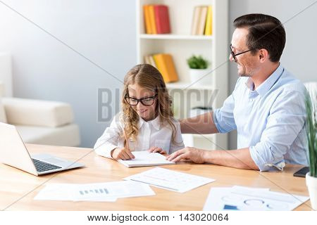 Successful since the childhood. Joyful satisfied man looking how her little cute daughter writing while sitting at the table in front of a laptop