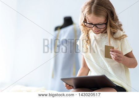 Lets make a choice. Joyful little girl sitting and looking at the tablet while smiling and holding a bank card