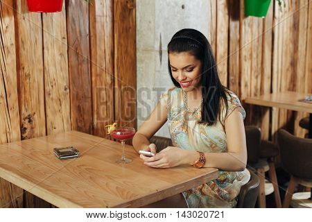 Young woman texting in a cafe on a smartphone