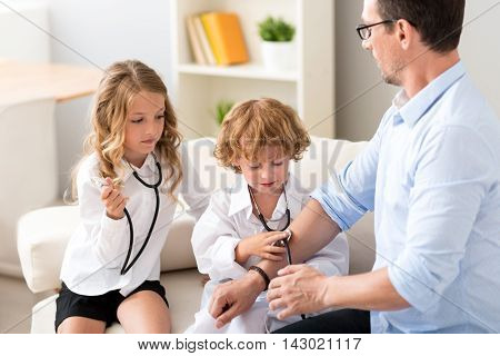 Stay alive. Thoughtful little boy and girl treating their father with a stethoscope on the couch