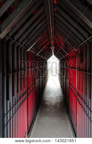 Mysterious dungeon tunnel with walls made of metal lit red