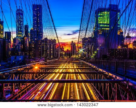 Sunset over the Brooklyn Bridge facing manhattan with lights of passing by cars underneath