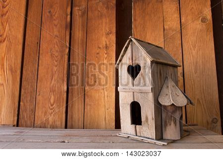 Horizontal image of old wooden birdhouse with heart-shaped window and room for copy.