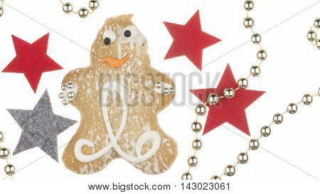 cheerful gingerbread man decorated with a pattern of sweet sugar fondant and sugar silver balls and stars and decorative gold beads on a white background isolated
