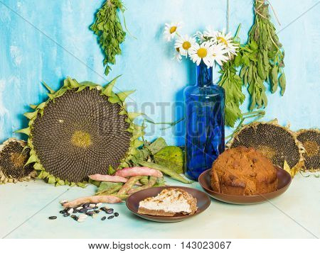 a rustic still life with sunflowers and ripe autumn bouquet of daisies in a blue glass bottle and delicious freshly baked pastries on a background of blue painted wall