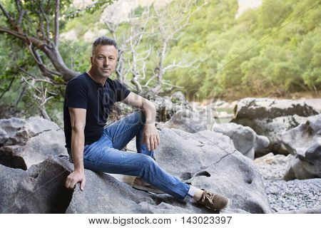 Outdoor male portrait. Man sitting on rocks near mountain river, image toned and noise added.