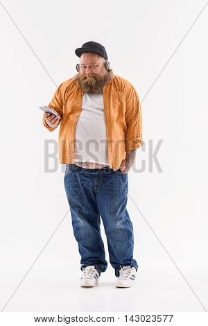 Bearded fat male hipster is listening to music and smiling. He is standing and holding smartphone. Isolated