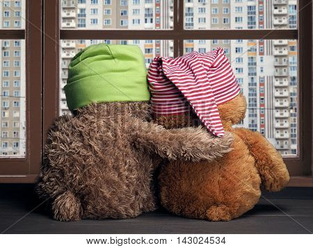 Two friends looking out the window at the windows of the house. Toys colorful hats bear cubs. Embrace the window. Concept - love friendship support dreams of a new home apartment