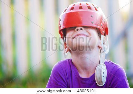child wears old hockey helmet and having fun. old hockey helmet slid the eye of a laughing boy
