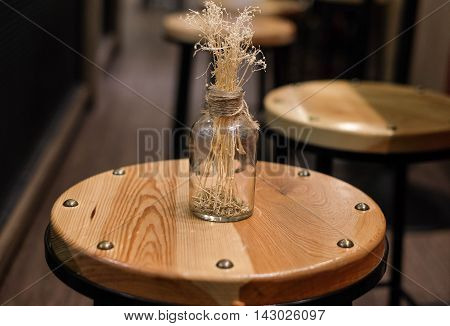 dry hay in the glass on the wood chair for interior decoration