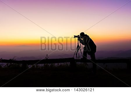 Silhouette Of Photographer Take A Photograph At View Point In Twilight