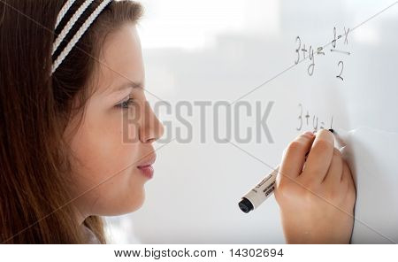Cute Preteen Schoolgirl Writing Letter On Whiteboard Studiously