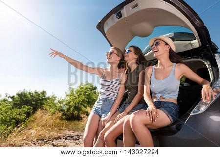 Have a look. Positive smiling young friends sitting and having fun near the car while expressing gladness