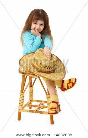Child Sits On An Old Wooden Chair With Hat