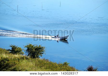 Man in a white boat with engine speeding on sea water. Picture taken from land with land visible.