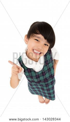 Pointing showing little girl. Humorous high angle of a grinning little girl pointing to the left of the frame with her finger. on white background