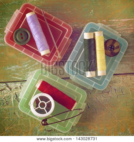 Arrangement of Plastic Sewing Boxes Pins Needles and Thread Spools closeup on Cracked Wooden background. Retro Styled