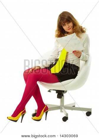 Young Woman Reads Document In White Chair