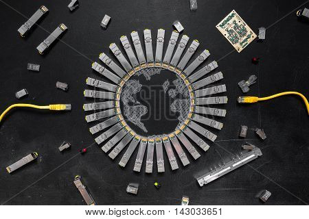 Electrical Internet SFP network modules as the shape of Earth network switch RJ45 ethernet cables RJ45 connectors circuit board with microchips diodes are on the black background