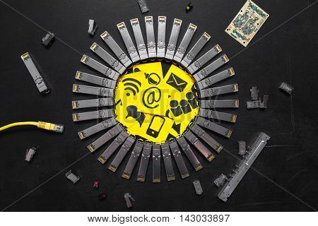 Electrical Internet SFP network modules RJ45 ethernet cable RJ45 connectors circuit board with microchips diodes and yellow stickers with telecommunications icons are on the black background