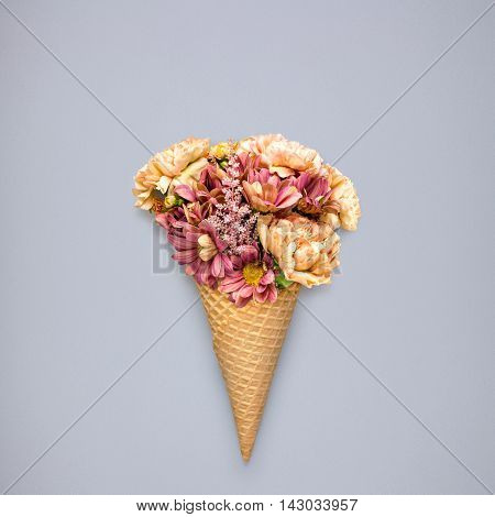 Creative still life of an ice cream waffle cone with flowers on grey background.