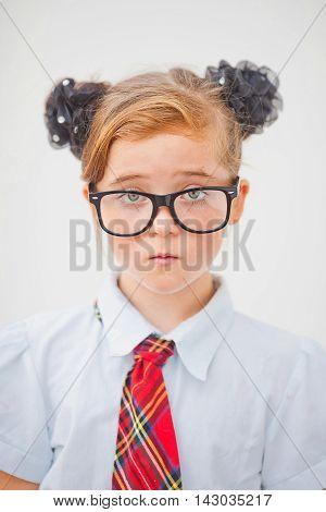 Pretty teen girl wearing school uniform and school bag.