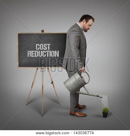 Cost Reduction text on  blackboard with businessman watering plant