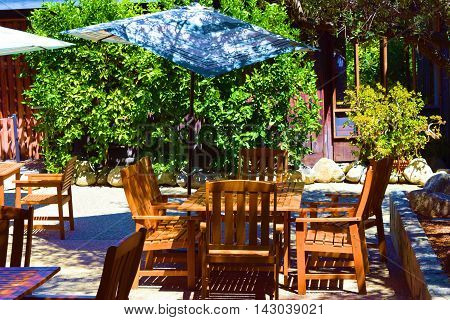 Modern style wooden outdoor furniture including tables, chairs, and umbrellas taken at a courtyard in a garden