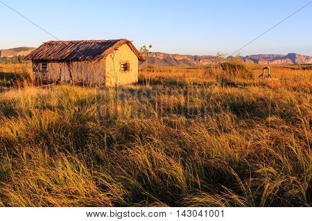 House In An African Landscape At Sunrise