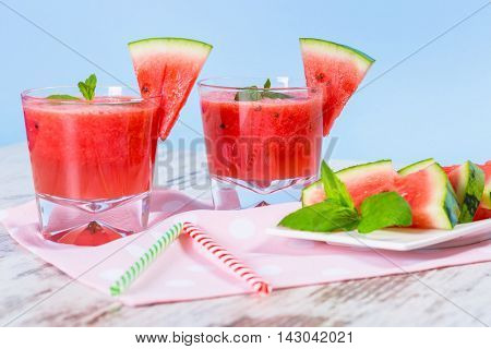 Glasses of watermelon smoothie on a wooden table