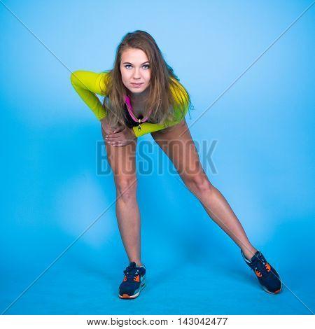 Posing sport girl on start-up posing on blue background