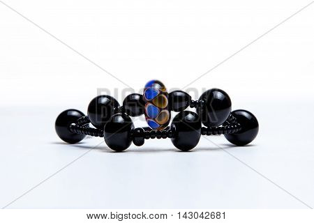 Bracelet with black glass beads on white background