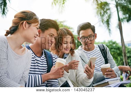 Cheerful classmates looking at screen of smartphone