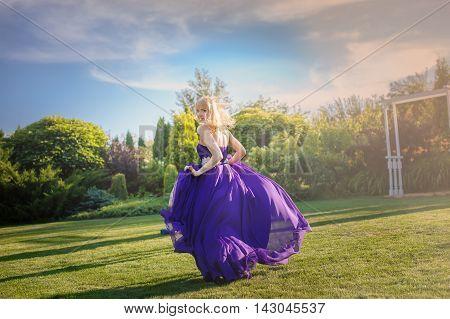 Blonde gorgeous woman in long purple luxurious dress posing in garden. Dress fluttering on wind.