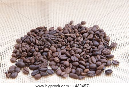 Fresh roasted brown coffee beans on a fabric burlap