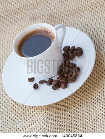 Cup of aromatic espresso coffee and roasted fresh brown beans