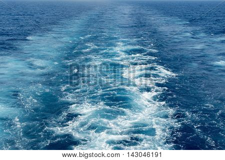 The wake of a cruise ship sailing on the ocean with blue water and waves