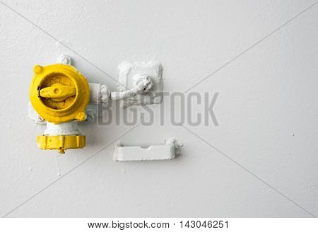 Yellow control valve industrial switch on a white metallic surface