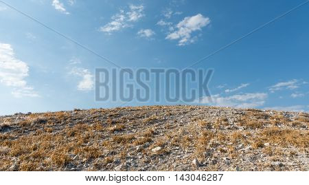 Deserted sloped cliff with rocks and yellow dry grass and blue cloudy sky late in Summer.