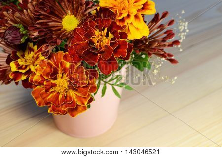 Marigold and chrysanthemum red and orange flowers bouquet on a wooden background