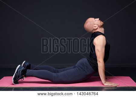 Young fitness man performing cobra pose on the mat