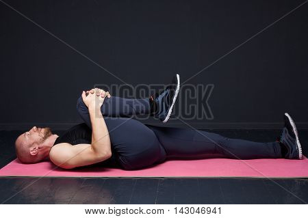 Young fitness man doing leg stretching on the mat