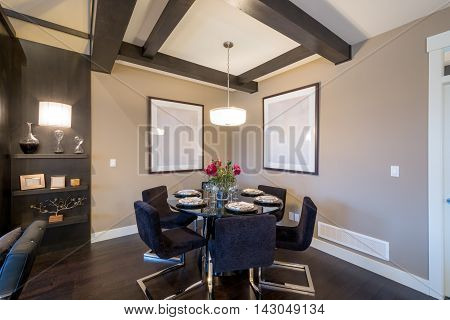 Modern round dining room table set for dinner in a luxury house. Interior design.