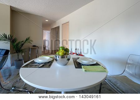 Bright dining room with a table set for dinner. Interior design.