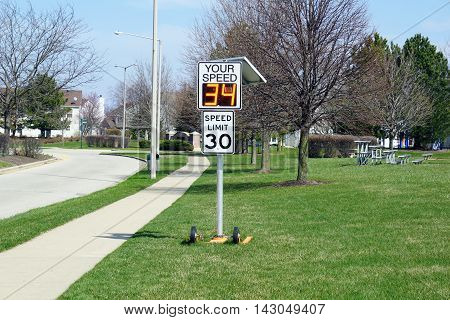 JOLIET, ILLINOIS / UNITED STATES - MARCH 26, 2016: A radar speed sign indicates that a vehicle is approaching at 34 miles per hour, and exceeding the posted speed limit.