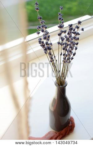 Dried lavender in the brown glass vase on a window sill