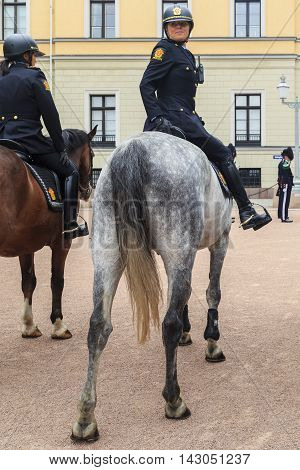 OSLO NORWAY - JULY 1 2016: A woman police officer on horseback accompanied by changing of the guard ceremony at the Royal Palace.