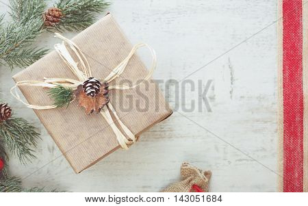 Christmas gift wrapped in brown paper.  Vintage toned image, top view, blank space